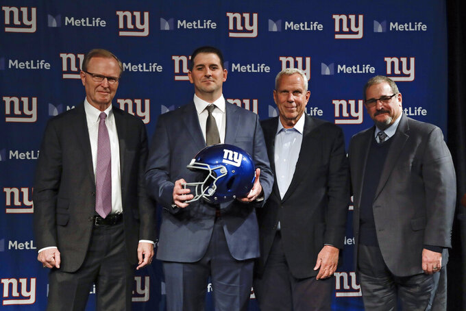 New York Giants new NFL football head coach Joe Judge, second from left, poses for photographs with New York Giants chairman and executive vice president Steve Tisch, second from right, New York Giants CEO John Mara, left, and New York Giants general manager Dave Gettleman, right, after a news conference Thursday, Jan. 9, 2020, in East Rutherford, N.J. (AP Photo/Frank Franklin II)