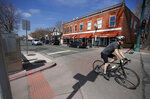 A bicyclist rolls down the empty main street as a statewide stay-at-home order takes effect to reduce the spread of the new coronavirus Thursday, March 26, 2020, in Arvada, Colo. The new coronavirus causes mild or moderate symptoms for most people, but for some, especially older adults and people with existing health problems, it can cause more severe illness or death. (AP Photo/David Zalubowski)
