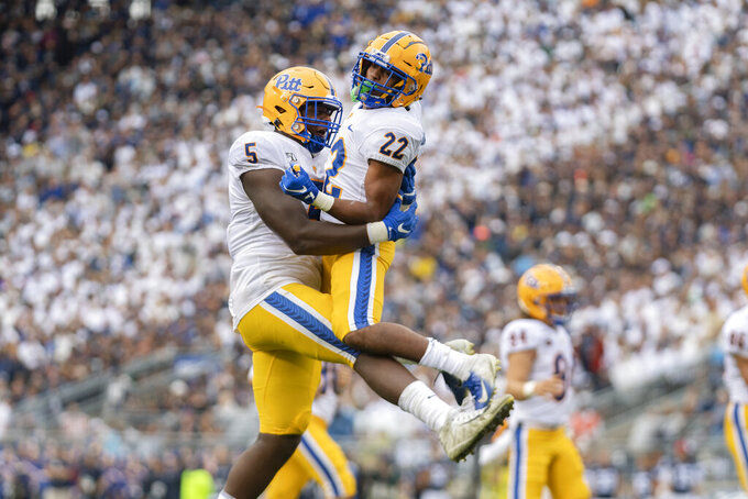 Pittsburgh running back Vincent Davis (22) celebrates his touchdown with teammate Deslin Alexandre (5) in the first quarter of an NCAA college football game against Penn State in State College, Pa., on Saturday, Sept. 14, 2019. (AP Photo/Barry Reeger)
