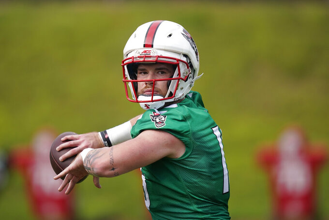 FILE - In this Aug. 4, 2021, file photo, North Carolina State quarterback Devin Leary passes during NCAA college football practice in Raleigh, N.C. Leary is returning from a leg injury that sidelined him for much of last season. (AP Photo/Gerry Broome, File)
