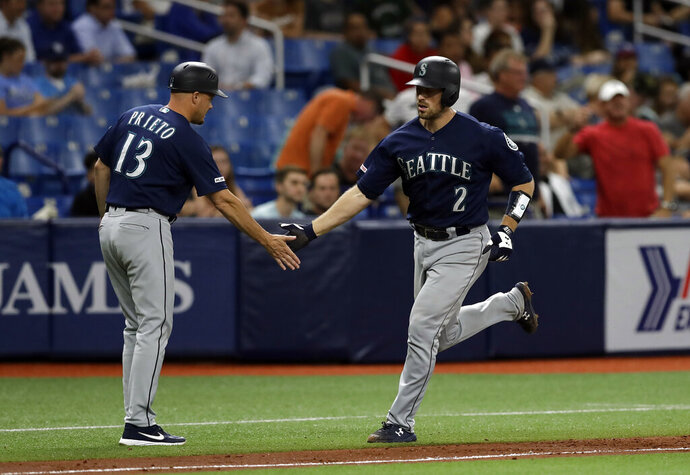 Seattle Mariners' Tom Murphy (2) shakes hands with third base coach Chris Prieto (13) after Murphy hit a two-run home run off Tampa Bay Rays relief pitcher Jalen Beeks during the sixth inning of a baseball game Tuesday, Aug. 20, 2019, in St. Petersburg, Fla. (AP Photo/Chris O'Meara)