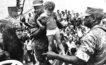 FILE- In this May 10, 1980, file photo, a U.S. Marine helps a young Cuban child off a refugee boat in Key West, Fla. Throughout history, the United States has used all sorts of physical or mental exams for immigrants seeking just to get into the country outside of becoming a citizen. (AP Photo/Fernando Yovera, File)