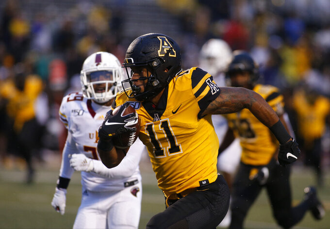 Appalachian State wide receiver Jalen Virgil (11) evades Louisiana Monroe safety Logan Latin (29) as he runs for a touchdown during the second half of an NCAA college football game  Saturday, Oct. 19, 2019, in Boone, NC. (AP Photo/Brian Blanco)