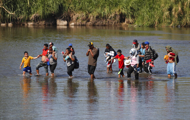 Central American migrants cross the Suchiate River from Mexico to Guatemala, near Tecun Uman, Guatemala, Tuesday, Jan. 21, 2020. Hundreds of Central American migrants are stranded in a sort of no-man's land on the river border between Guatemala and Mexico after running up against lines of Mexican National Guard troops deployed to keep them from moving en masse into the country and on north toward the U.S. on Monday. (AP Photo/Moises Castillo)