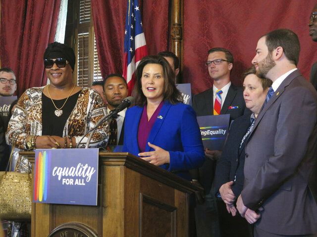 FILE - In this June 4, 2019, file photo, Michigan Gov. Gretchen Whitmer, center, joins with lawmakers and others calling for expanding the state's civil rights law to prohibit discrimination against LGBT people, in the Capitol building in Lansing, Mich. A ballot drive has turned in more than 483,000 signatures for the initiative to prohibit discrimination against LGBTQ people in Michigan by amending the state's civil rights law. If election officials determine roughly 340,000 are valid, the bill would be placed before the Republican-led Legislature, where similar legislation has long stalled. (AP Photo/David Eggert, File)