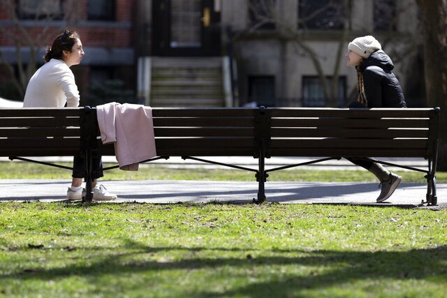 Two women practice social distancing while talking on Commonwealth Avenue Mall in Boston during the coronavirus outbreak Saturday, April 4, 2020. (AP Photo/Michael Dwyer)