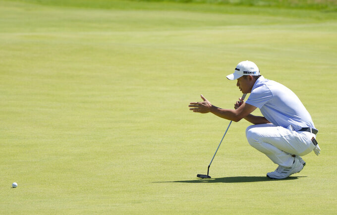United States' Collin Morikawa looks at the line of his putt on the 18th green during the second round of the British Open Golf Championship at Royal St George's golf course Sandwich, England, Friday, July 16, 2021. (AP Photo/Alastair Grant)