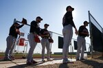From left to right, Cleveland Indians pitchers Dominic Leone, Logan Allen, Kyle Dowdy, Shane Bieber, and Carlos Carrasco wait their turn for their pitching session during spring training baseball workouts for pitchers and catchers Thursday, Feb. 13, 2020, in Avondale, Ariz. (AP Photo/Ross D. Franklin)