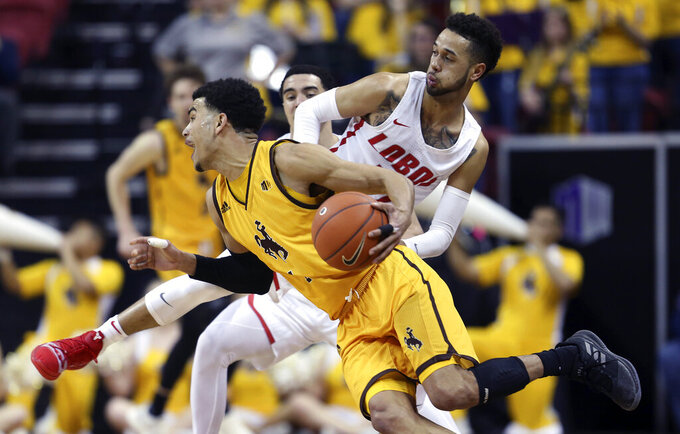Wyoming's Justin James drives past New Mexico's Anthony Mathis during the second half of an NCAA college basketball game in the Mountain West Conference tournament, Wednesday, March 13, 2019, in Las Vegas. (AP Photo/Isaac Brekken)