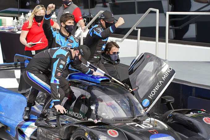 Filipe Albuquerque, of Portugal, drives the Acura DPi to Victory Lane as teammates Alexander Rossi, left, Ricky Taylor, Helio Castroneves, and team owner Wayne Taylor celebrate after winning the Rolex 24 hour auto race at Daytona International Speedway, Sunday, Jan. 31, 2021, in Daytona Beach, Fla. (AP Photo/John Raoux)