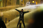 Anti-government protesters are sprayed by a water cannon as they clash with the riot police during ongoing protests in Beirut, Lebanon, Wednesday, Jan. 22, 2020.  Lebanon's new government has held its first meeting a day after it was formed following a three-month political vacuum. (AP Photo/Bilal Hussein)