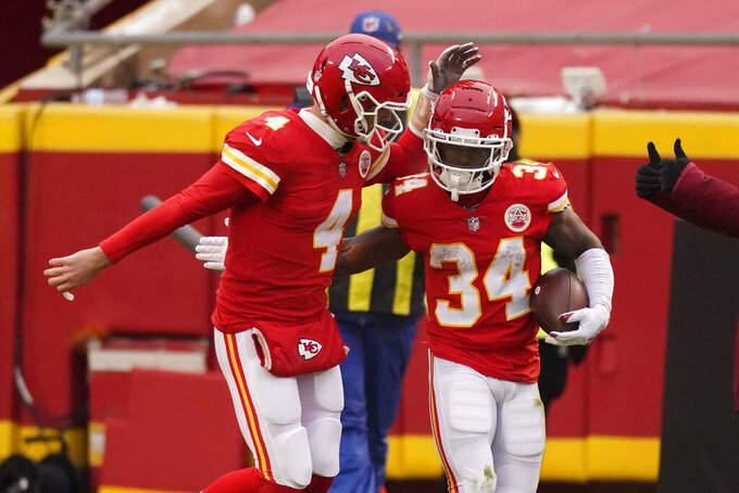 Kansas City Chiefs running back Darwin Thompson (34) celebrates with quarterback Chad Henne (4) after scoring on a 1-yard touchdown run during the first half of an NFL football game against the Los Angeles Chargers, Sunday, Jan. 3, 2021, in Kansas City. (AP Photo/Charlie Riedel)