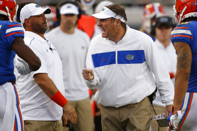 Florida coach Dan Mullen yells at his wide receivers coach Billy Gonzales in the second half of an NCAA college football game Saturday, Nov. 2, 2019, in Jacksonville, Fla. Georgia won 24-17.  (Joshua L. Jones/Athens Banner-Herald via AP)