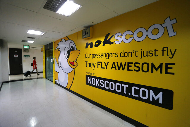 Flight crew walks past a giant poster of NokScoot office at Don Muang airport in Bangkok, Thailand, Saturday, June 27, 2020. Thailand's low-cost carrier NokScoot, which is partly owned by Singapore Airlines, said its board of directors decided to liquidate the company as the coronavirus pandemic dimmed prospects for its recovery. (AP Photo/Nathathida Adireksarn)