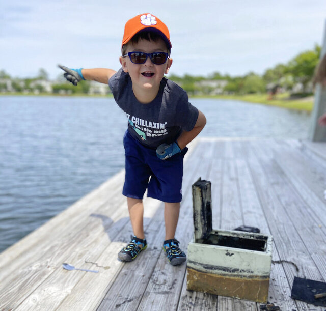 In this May 9, 2020, photo provided by Catherine Brewer, Knox Brewer stands next to a safe he pulled out of Whitney Lake in South Carolina. The 6-year-old was using a magnet attached to a string to fish for metal in the water when he reeled in a lockbox that police said was stolen from a woman who lived nearby eight years ago. (Catherine Brewer via AP)