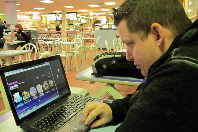 FILE - In this Nov. 21, 2013 file photo, Joseph Brennen of Ventnor N.J., logs on to a Harrah's online casino on his laptop from a highway rest area in Egg Harbor Township, N.J. on the first day of a test of Internet gambling in New Jersey. On Tuesday, March 17, 2020, many internet gambling providers said they've noticed a significant increase in business in the past week as many land-based casinos shut down due to the coronavirus. (AP Photo/Wayne Parry)