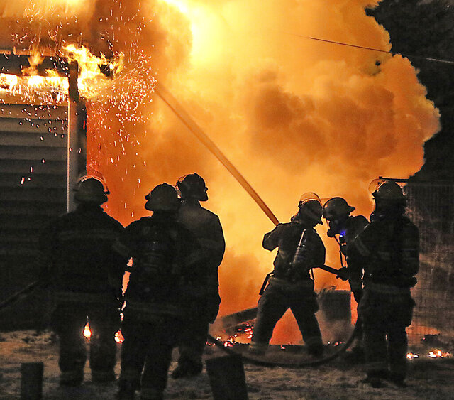 Yankton firefighters try to control a house fire west of Yankton, S.D., on Monday, Dec. 28, 2020.  No one was injured in the incident, but the fire rekindled early Tuesday and caused extensive damage. (Kelly Hertz/Yankton Press & Dakotan via AP)