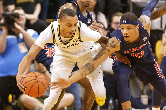 Auburn's Samir Doughty, right, tries to steal the ball from Missouri's Xavier Pinson, left, during the first half of an NCAA college basketball game Saturday, Feb. 15, 2020, in Columbia, Mo. (AP Photo/L.G. Patterson)