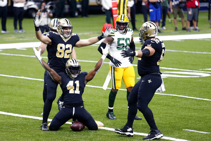 New Orleans Saints running back Alvin Kamara (41) celebrates his touchdown carry with tight end Adam Trautman (82) and offensive guard Nick Easton (62) as Green Bay Packers inside linebacker Christian Kirksey (58) watches, in the first half of an NFL football game in New Orleans, Sunday, Sept. 27, 2020. (AP Photo/Brett Duke)