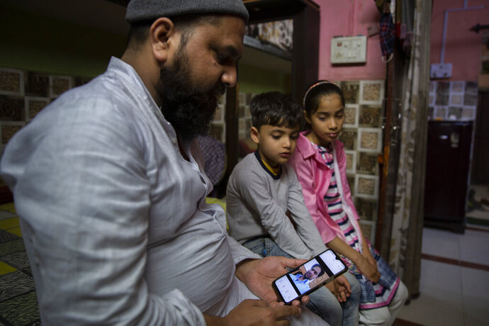 Haroon, holds a mobile phone as his nephew and niece look at the photograph of their father who was shot and killed by their Hindu neighbors during February 2020 communal riots, in North Ghonda, one of the worst riot affected neighborhood, in New Delhi, India, Friday, Feb. 19, 2021. As the first anniversary of bloody communal riots that convulsed the Indian capital approaches, Muslim victims are still shaken and struggling to make sense of their struggle to seek justice. (AP Photo/Altaf Qadri)