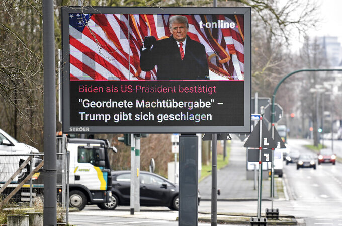 A large news screen beside a street in Essen, Germany, showing US president Donald Trump, and a headline reading 'Biden as US president confirmed, orderly transfer of power - Trump declares defeat' on Thursday, Jan. 7, 2021. (AP Photo/Martin Meissner)