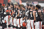 Members of the Cleveland Browns stand for the national anthem as it rains and hails before an NFL football game against the Houston Texans, Sunday, Nov. 15, 2020, in Cleveland. The game was delayed due to lightning. (AP Photo/David Richard)