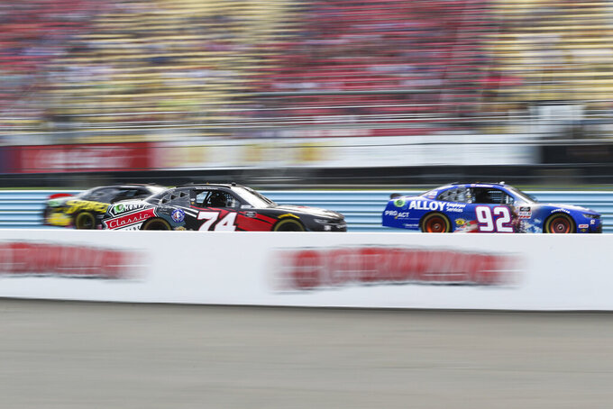 Josh Williams (92), driver Bayley Currey (74), and Jade Buford, left, race by the grandstand in the final laps of a NASCAR Xfinity Series auto race at Watkins Glen International in Watkins Glen, N.Y., on Saturday, Aug. 7, 2021. (AP Photo/Joshua Bessex)