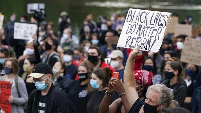 A man holds up a sign during a protest, Tuesday, Sept. 29, 2020, in Cleveland. Racism trips up Black police candidates at the very beginning of the application process and as they seek later promotion, complicating efforts to make law enforcement agencies more diverse, say numerous experts and Black police associations and officers. (AP Photo/Tony Dejak)