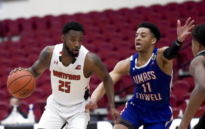 Hartford's Traci Carter (25) is guarded by UMass-Lowell's Obadiah Noel (11) during an NCAA college basketball game in the championship of the  America East conference tournament Saturday, March 13, 2021, in Hartford, Conn. (Kassi Jackson/Hartford Courant via AP)