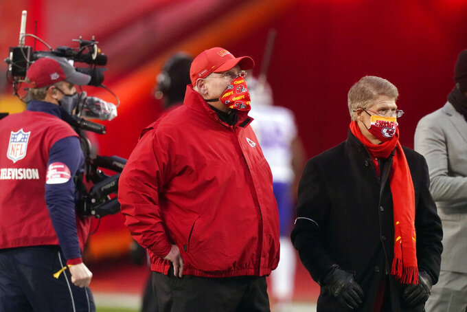 Kansas City Chiefs head coach Andy Reid and Chiefs owner Clark Hunt, right, watch players warm up before the AFC championship NFL football game against the Buffalo Bills, Sunday, Jan. 24, 2021, in Kansas City, Mo. (AP Photo/Charlie Riedel)