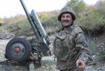 An ethnic Armenian soldier smiles as he speaks to journalists at a fighting position on the front line, during a military conflict against Azerbaijan's armed forces in the separatist region of Nagorno-Karabakh, Wednesday, Oct. 21, 2020. Armenia's prime minister has urged citizens to sign up as military volunteers to help defend the country amid the conflict with Azerbaijan over the disputed territory of Nagorno-Karabakh as intense fighting has raged for a fourth week with no sign of abating. (Sipan Gyulumyan, Armenian Defense Ministry Press office/PAN Photo via AP)