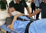 A British pilot, identified by the official Vietnam News Agency as Stephen Cameron, is carried on a stretcher from a hospital in Ho Chi Minh city, Vietnam Saturday, July 11, 2020. The pilot who was Vietnam's most critical COVID-19 patient has been discharged from a hospital, less than a week after doctors said he was virus-free and healthy enough to return home to Scotland. Vietnam has gone all out to save the 42-year-old man. (AP Photo/Hieu Dinh)