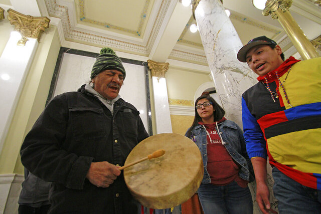A protester plays a drum and sings at the South Dakota Capitol in Pierre, on Tuesday, Feb. 18, 2020, in protest of the House voting on a bill that would criminalize the