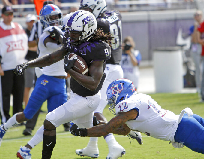 TCU Horned Frogs wide receiver Te'Vailance Hunt (9) is tackled by Kansas Jayhawks safety Jeremiah McCullough (12) after a reception in the first half. The Kansas Jayhawks played the TCU Horned Frogs at Amon Carter Stadium in Fort Worth, Texas Saturday, Sept. 28, 2019.   (David Kent/Star-Telegram via AP)