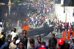 CORRECTS ARREST DATE - FILE - In this Feb. 12, 2019 file photo, an overturned car burns during a protest demanding the resignation of Haitian President Jovenel Moise in Port-au-Prince, Haiti. The Feb. 17, 2019 arrest of a group of armed contractors', their unexplained release and the still-murky nature of their mission have helped fuel political chaos in Haiti, where Moise has faced months of protests over his government's failure to prosecute the theft and mismanagement of $2 billion in subsidized oil aid from Venezuela under the administration of his predecessor and political patron, Michel Martelly. (AP Photo/Dieu Nalio Chery, File)