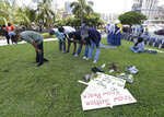 Muslim protesters pray before joining a demonstration in the death of George Lloyd , Sunday, May 31, 2020, in Miami. (AP Photo/Wilfredo Lee)