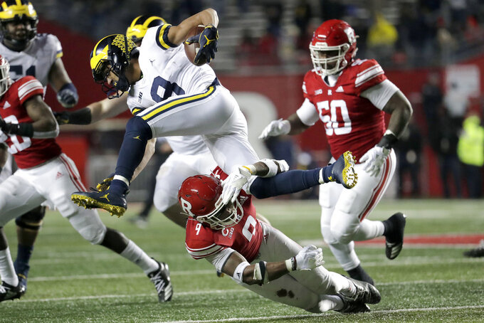 Michigan wide receiver Ronnie Bell, top, tries to leap over the tackle of Rutgers defensive back Saquan Hampton (9) during the second half of an NCAA college football game, Saturday, Nov. 10, 2018, in Piscataway, N.J. (AP Photo/Julio Cortez)