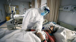 An elderly woman with COVID-19 is comforted by a doctor at a hospital in Wuhan, China in a scene from the documentary