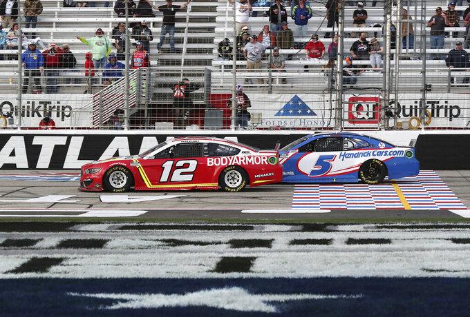 Ryan Blaney (12) rebasa a Kyle Larson a ocho vueltas del final para encaminarse a un triunfo en la carrera de la Copa Nascar en el Atlanta Motor Speedway, el domingo 21 de marzo de 2021, en Hampton, Georgia. (Curtis.Compton/Atlanta Journal-Constitution via AP)