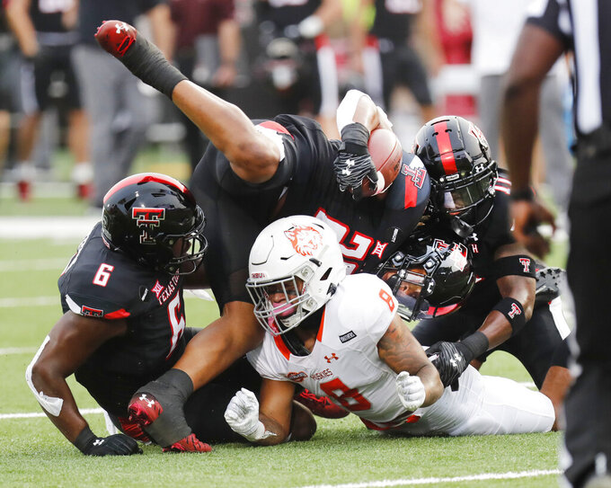Texas Tech's Kosi Eldridge carries the ball and lands atop Houston Baptist's Colton Manning (8) in the first half of an NCAA college football game, Saturday, Sept. 12, 2020, in Lubbock, Texas. (AP Photo/Mark Rogers)