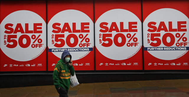 A woman wearing a face covering walks past a shop window in London, Thursday, Jan. 14, 2021 during England's third national lockdown to curb the spread of coronavirus. (AP Photo/Kirsty Wigglesworth)