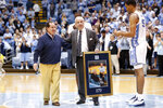 North Carolina coach Roy Williams is presented with a photograph of himself with Dean Smith by players Brandon Robinson and Garrison Brooks, right, following an NCAA college basketball game against Yale in Chapel Hill, N.C., Monday, Dec. 30, 2019. Williams tied Dean Smith with 879 careers wins. Scott Smith, son of the late Dean Smith, is seen at left. (AP Photo/Gerry Broome)