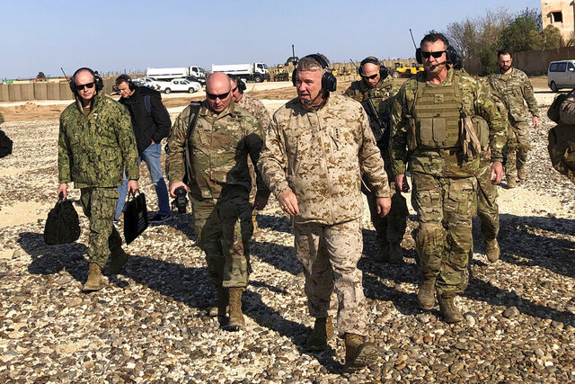 Gen. Frank McKenzie, center front, the top U.S. commander for the Middle East, walks as he visits a military outpost in Syria, Saturday, Jan. 25, 2020. McKenzie made the unannounced visit to Syria, traveling to five different military outposts to meet with troops, hear from commanders and talk with the leader of the Syrian Democratic Forces. (AP Photo/Lolita Baldor)