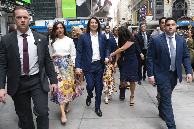 Vladimir Tenev, CEO and co-founder of Robinhood, center, walks with his wife Celina in New York's Times Square following his company's IPO, Thursday, July 29, 2021. Robinhood's stock will begin trading Thursday on Wall Street, the very place the online brokerage has rattled with its stated goal of democratizing finance.(AP Photo/Mark Lennihan)