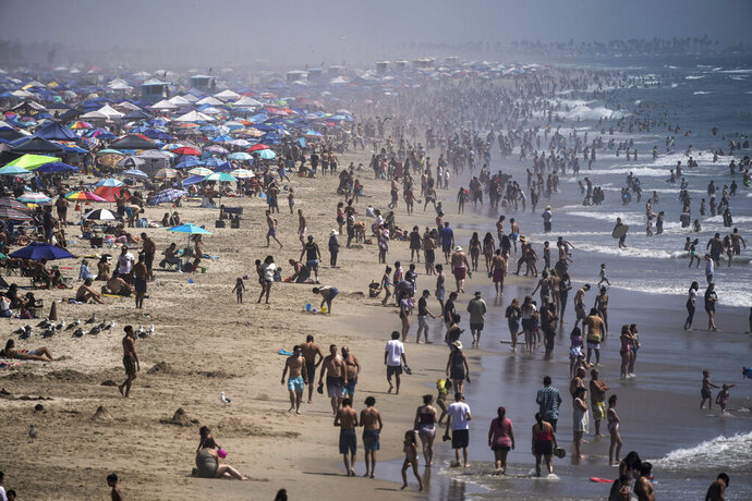 FILE - In this Saturday, Sept. 5, 2020 file photo, people crowd the beach in Huntington Beach, Calif., as the state swelters under a heat wave. On Wednesday, Oct. 14, 2020, the U.S. National Oceanic and Atmospheric Administration said the Earth reached a record hot September, saying that there's nearly a two-to-one chance that 2020 will end up as the globe's hottest year on record. (AP Photo/Jae C. Hong)