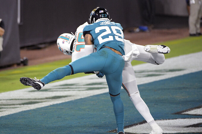 Miami Dolphins wide receiver Preston Williams, back left, catches a pass in the end zone of a touchdown as Jacksonville Jaguars strong safety Josh Jones (29) tires to defend during the first half of an NFL football game, Thursday, Sept. 24, 2020, in Jacksonville, Fla. (AP Photo/Phelan M. Ebenhack)