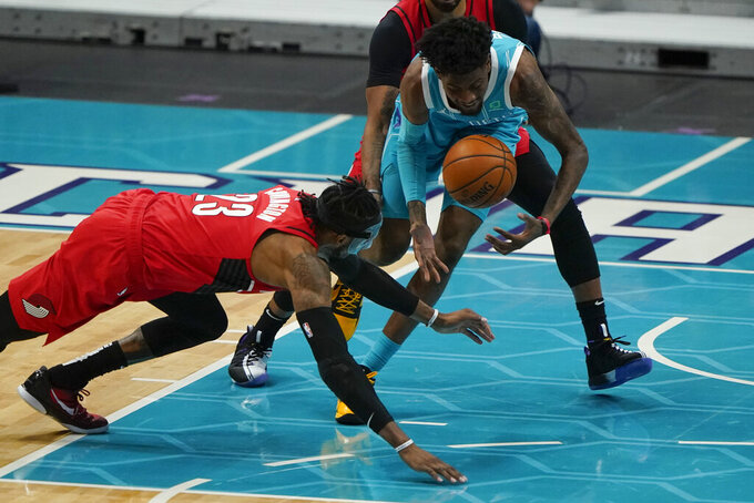 Portland Trail Blazers forward Robert Covington and Charlotte Hornets forward Jalen McDaniels battle for a loose ball during the first half in an NBA basketball game on Sunday, April 18, 2021, in Charlotte, N.C. (AP Photo/Chris Carlson)