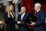 Sen. Kelly Loeffler, R-Ga., left, with her husband Jeffrey Sprecher, center, participates in a re-enactment of her swearing-in Monday Jan. 6, 2020, by Vice President Mike Pence in the Old Senate Chamber on Capitol Hill in Washington. (AP Photo/Jacquelyn Martin)