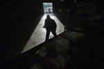 FILE- In this Dec. 15, 2014, file photo a worker checks packages on a conveyer belt before being loaded onto trucks for delivery at a FedEx Express facility in Marietta, Ga. FedEx reports financial results on Tuesday, March 19, 2019. (AP Photo/David Goldman, File)