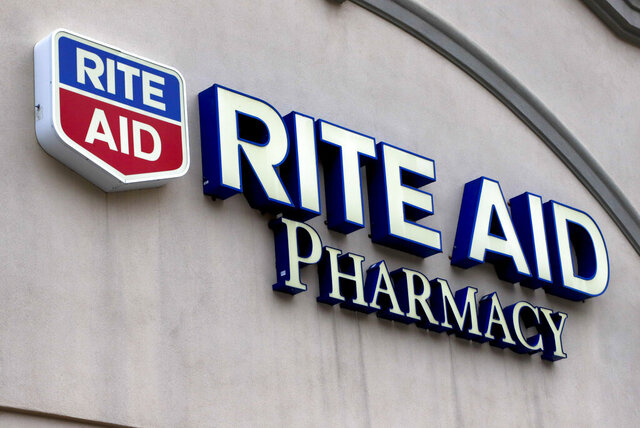 FILE - This April 14, 2020, file photo shows the sign on a Rite Aid Pharmacy in Pittsburgh, Pa. Customers pumped up Rite Aid sales of sanitizers, wipes and liquor, helping the drugstore chain deliver a better-than-expected fiscal first-quarter performance. Company shares started climbing early Thursday, June 25, 2020, after Rite Aid said its loss shrank to $63.5 million from $99.7 million in the previous year's quarter. The results topped analyst expectations.  (AP Photo/Gene J. Puskar, File)